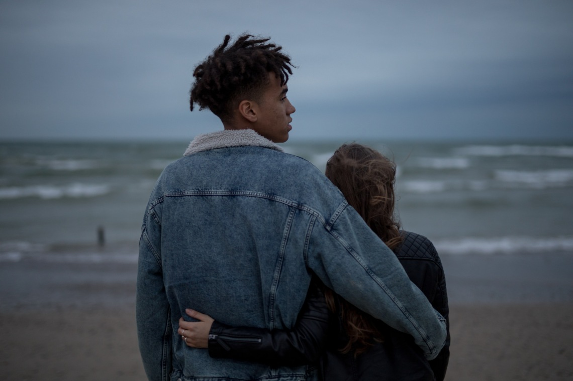 young couple arms around each other on the beach