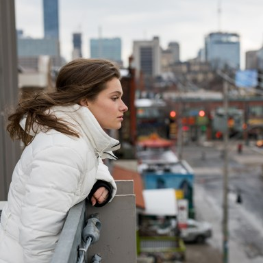 girl in a white coat looking over the city