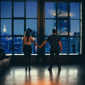 couple facing window holding hands