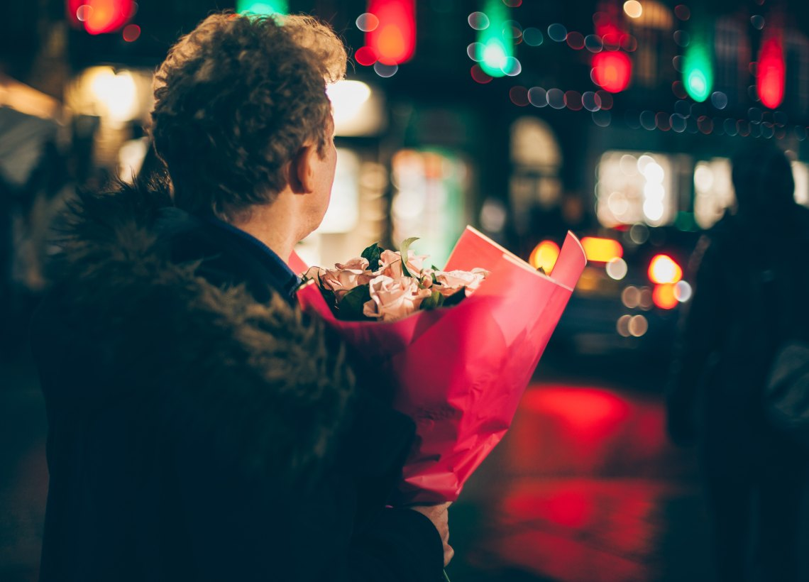 A man holds flowers in the night with lights blurring around him