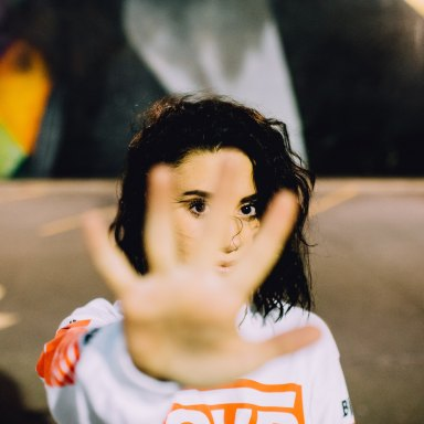 Woman stands in front of the camera, holding her hand in front of her face
