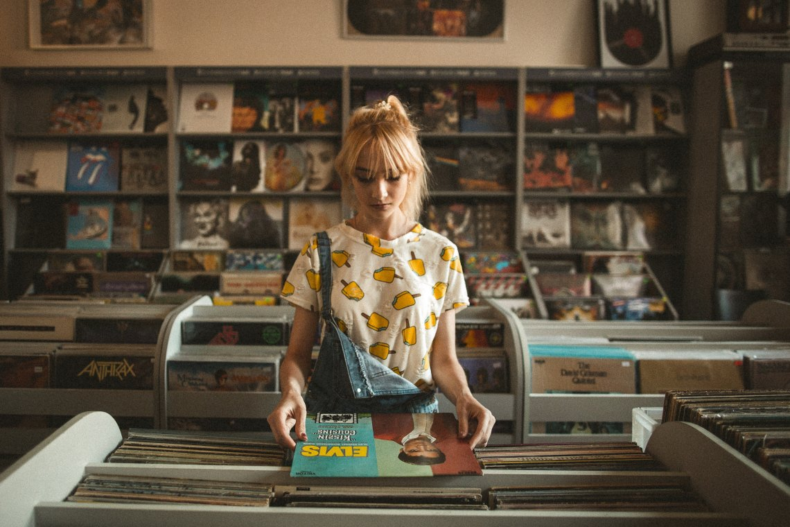 sad girl looking at vinyl records