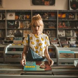 sad girl looking at vinyl records