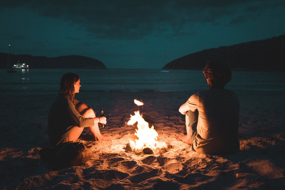 couple sitting together at bonfire