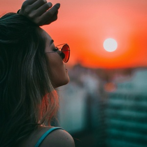 Woman standing alone by sunset