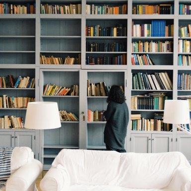 Woman walking through bookshelves