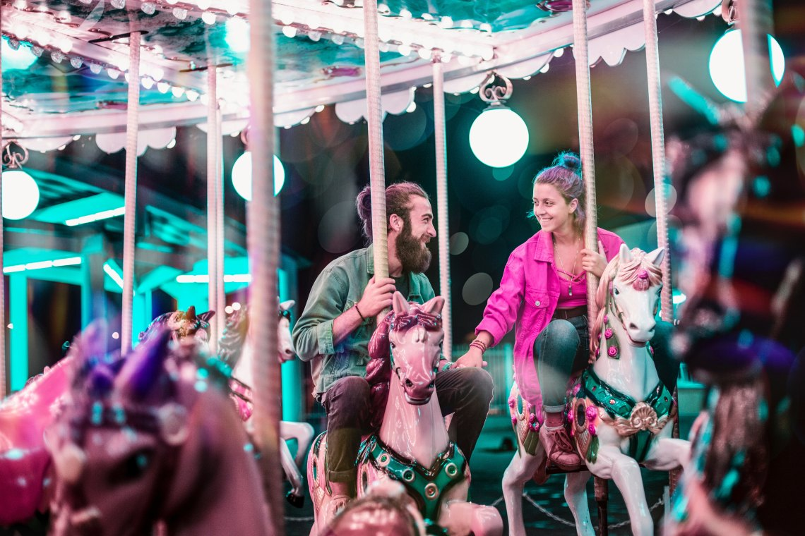 cute couple on carousel holding hands