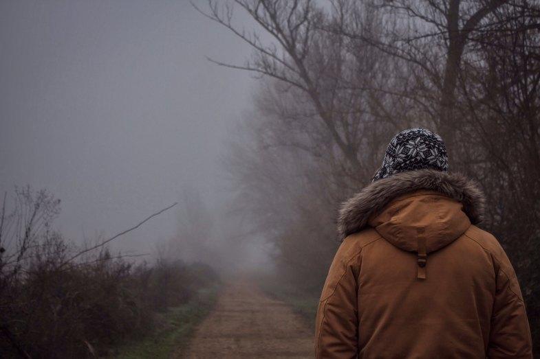 A man walks down a foggy, shadowy path into the woods