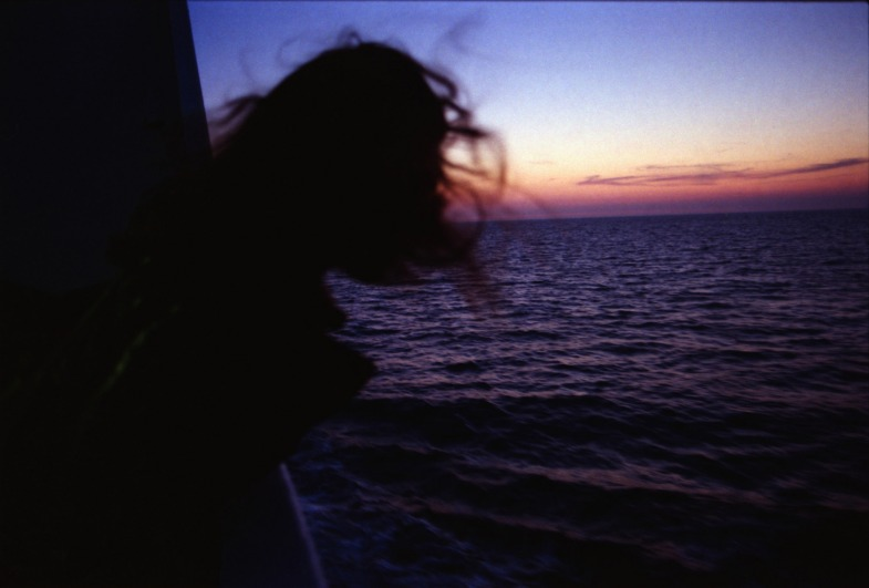 Girl on a boat leaning out to watch the sunset