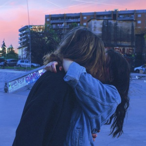 Couple kissing, embracing surrounded by concrete and graffiti