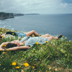 Two girls laying in the yellow flower speckled grass on an ocean bluff