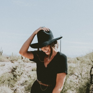 Girl in all black in the desert holding down the hat on her head, cactus cacti