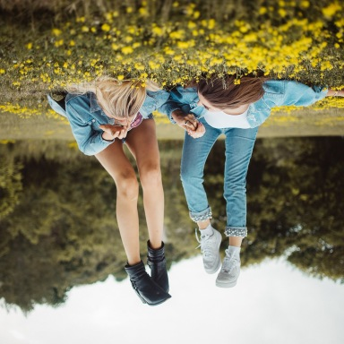 Upside down best friends laying in the grass with yellow flowers, being young, enjoying summer, happy best girl friends, friendship sisters, holding hands, hanging out, nature outdoors happy good times
