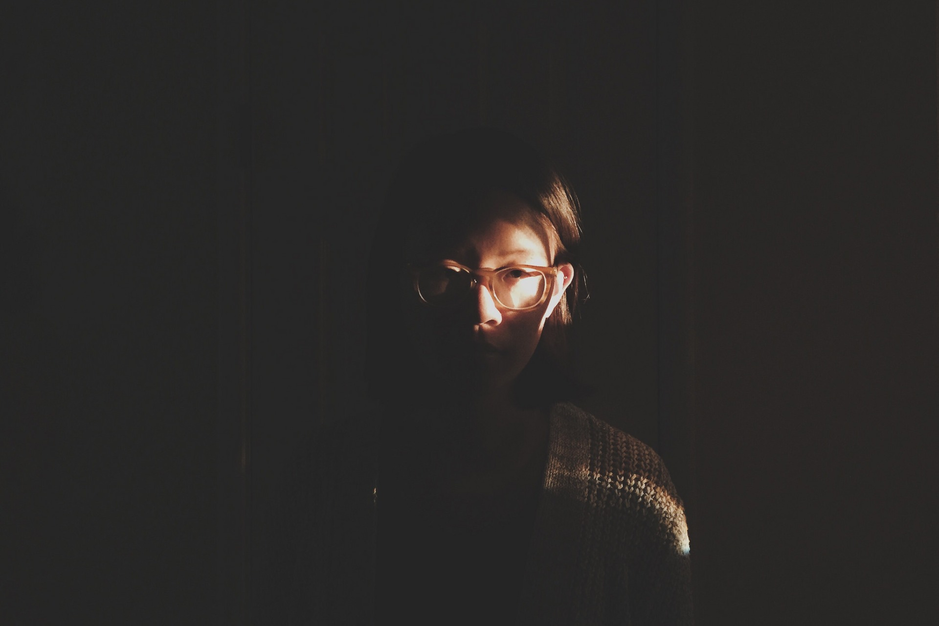 girl in the dark shadows with sun beaming on her face and glasses, thinking, hesitant, in the moment, reflecting