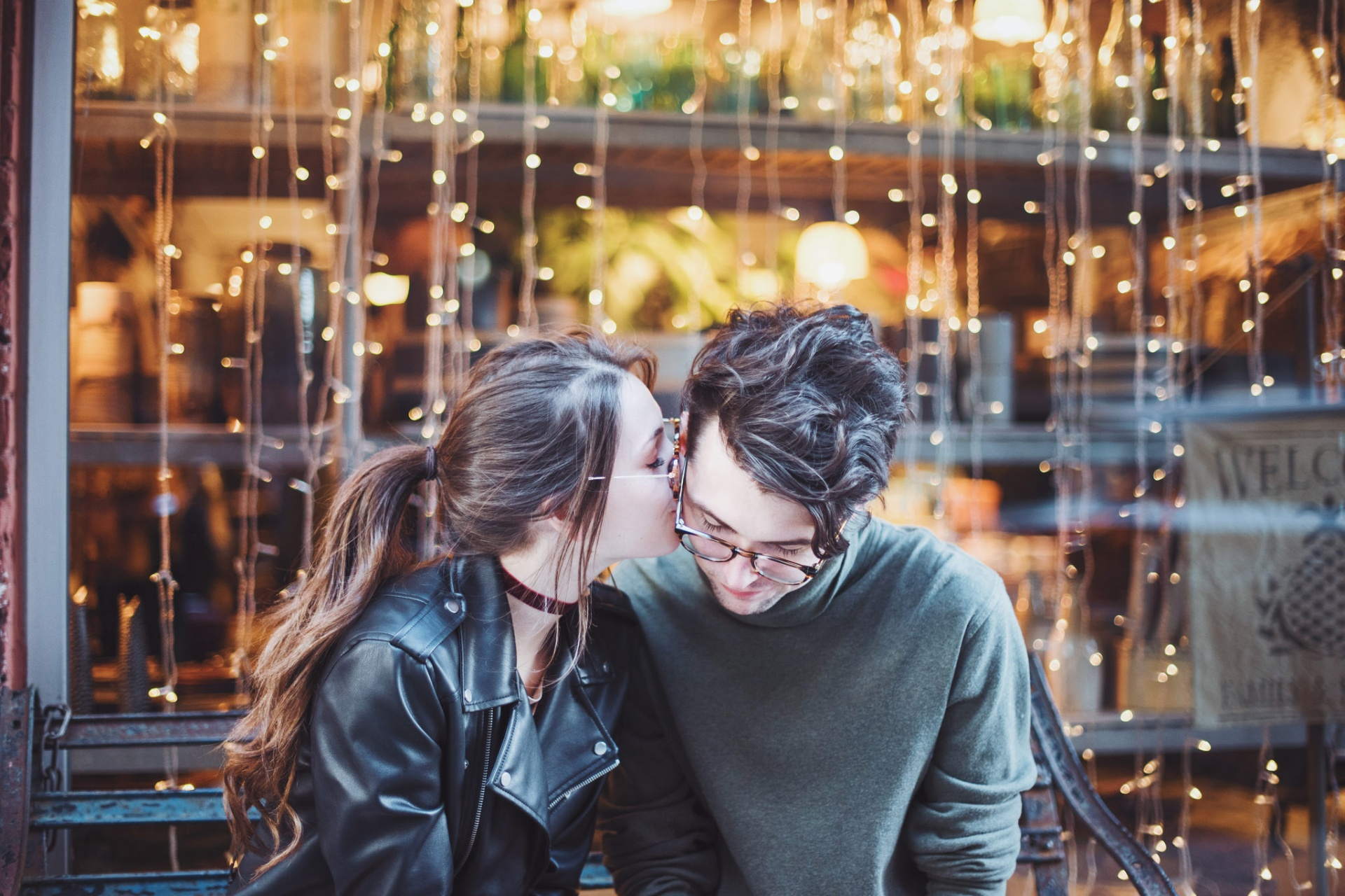 couple kissing in front of lights