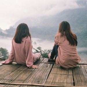 Two brunette girls in matching dusty rose pink shirts sitting on a rickety wooden platform overlooking misty mountains