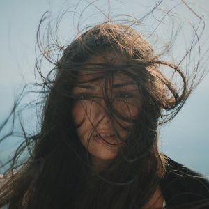 woman standing in sun with windblown hair