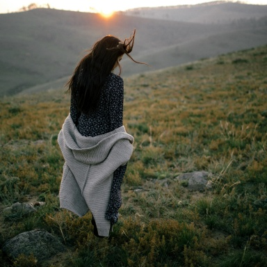 Girl taking a leisurely walk through rocky rough grasses and the sun is setting over the hills