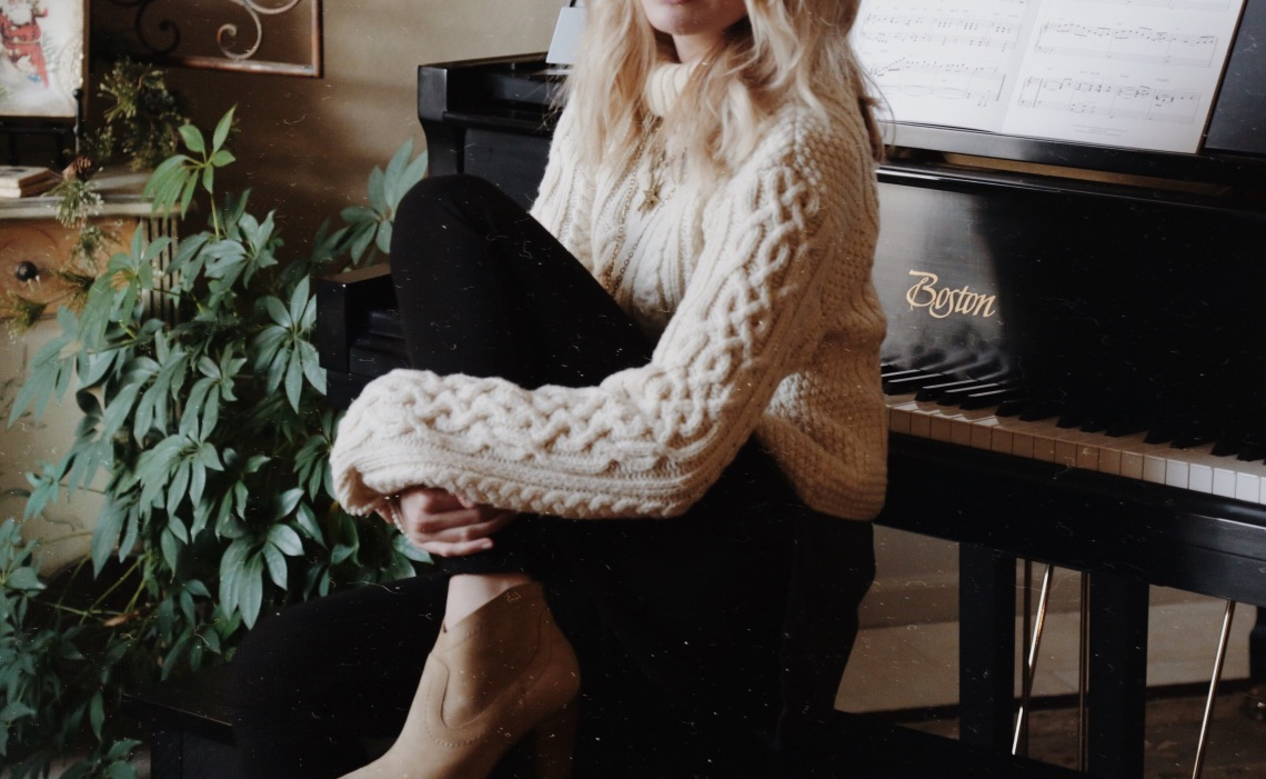 woman sitting in comfy sweater in front of piano