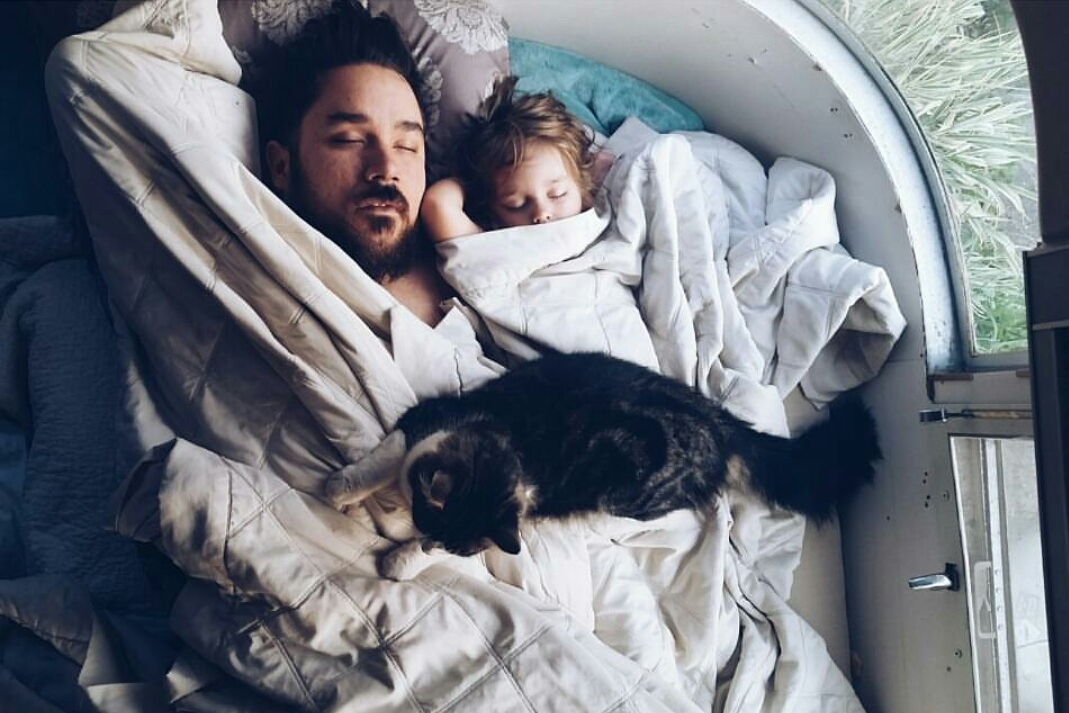 dad and daughter sleeping with cat