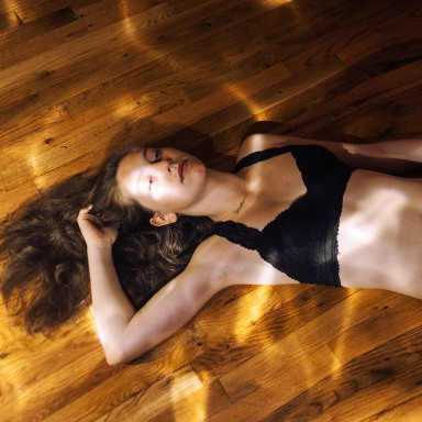 brunette laying on floor in black bra