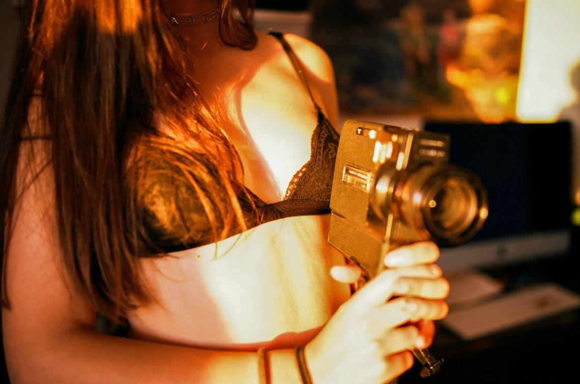 Close up of pretty woman in black bra pointing a camera like a gun