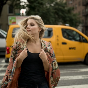 woman walking in front of taxi tossing hair