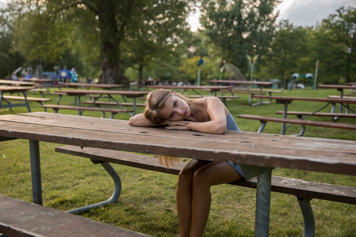 Damsel in Distress Solitarily Rests Her Head on the Picnic Table