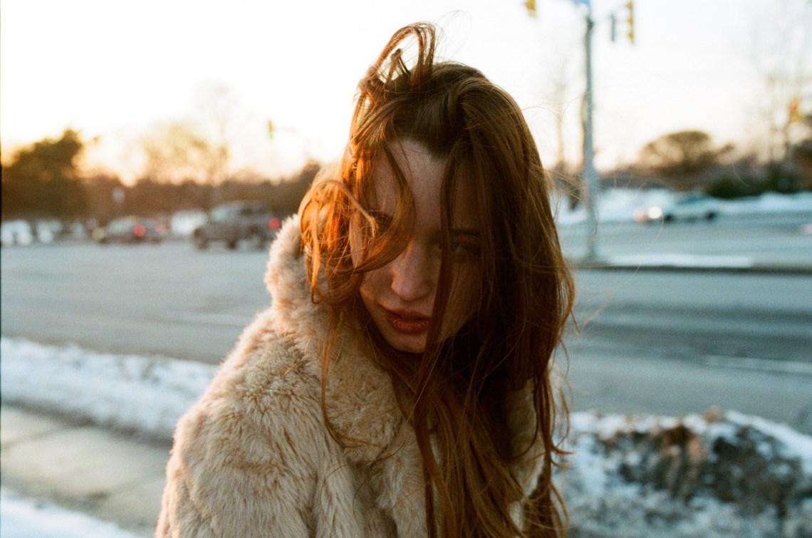 woman walking along street in winter