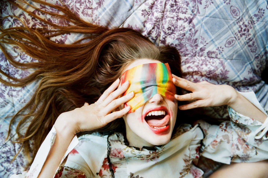 Girl playing with colorful fabric on her face