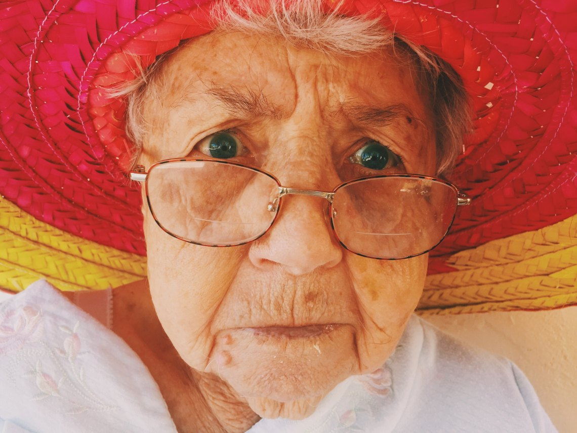 A grandma stares into the Camera with her glasses and red hat