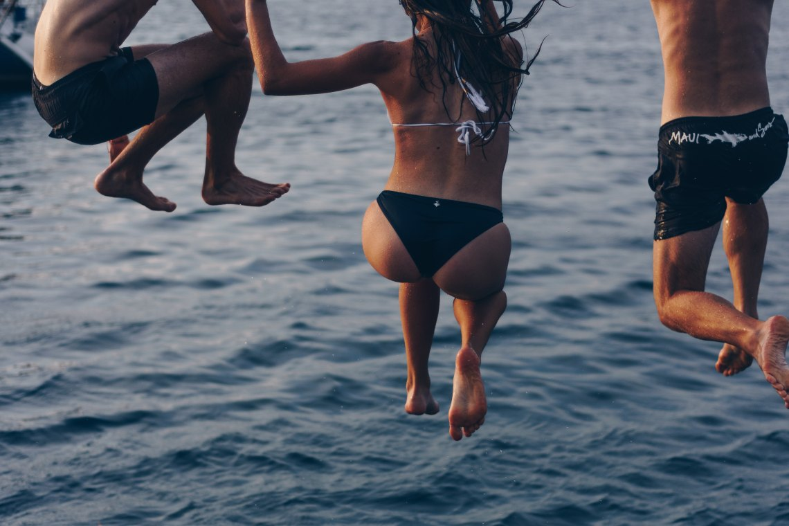 Three people jumping off a dock into the water