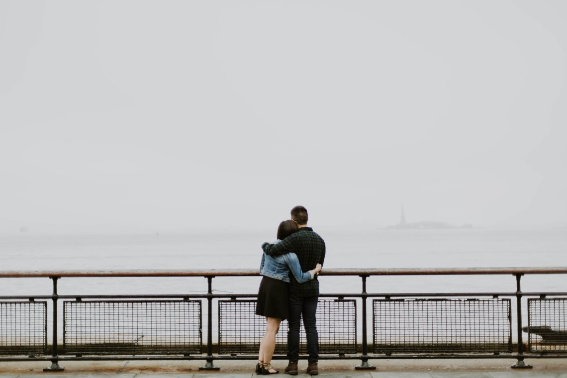 Woman and man hold each other while they stand on a bridge, staring out into the unknown together