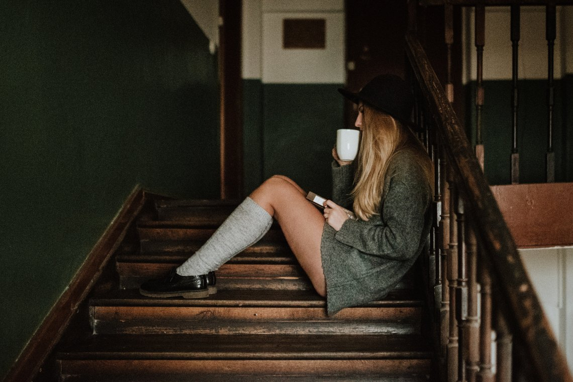woman sitting on stairs drinking coffee