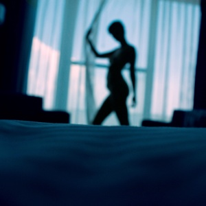 A woman, naked, walking in front of her window, only showing her silhouette