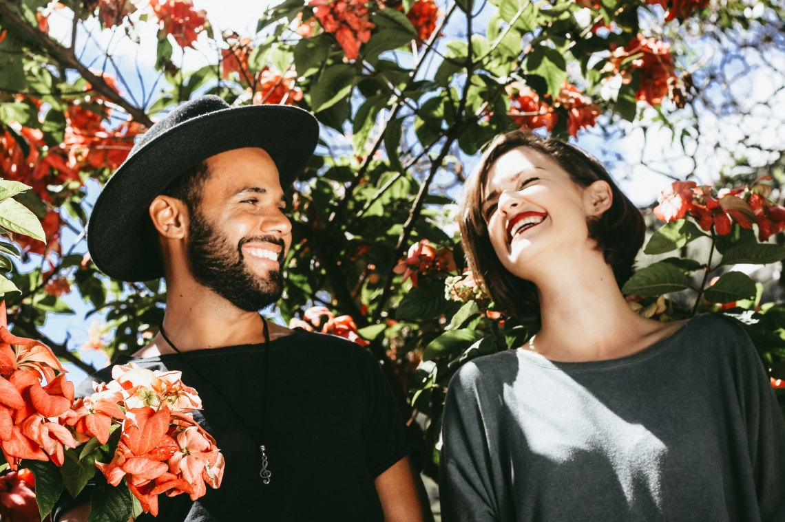 A man in a hate and a woman laugh as they walk through a tree full of flowers