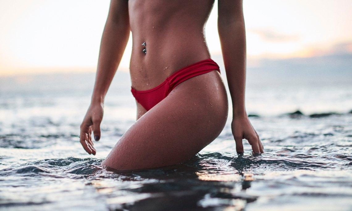 A thin woman in a red bikini walking in the ocean wateri