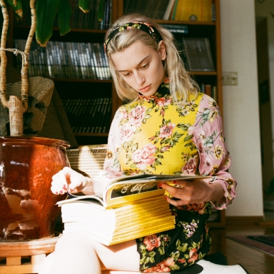 woman reading a ton of magazines
