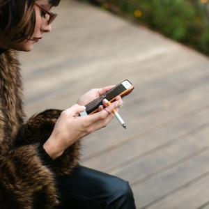 woman smoking cigarette on phone