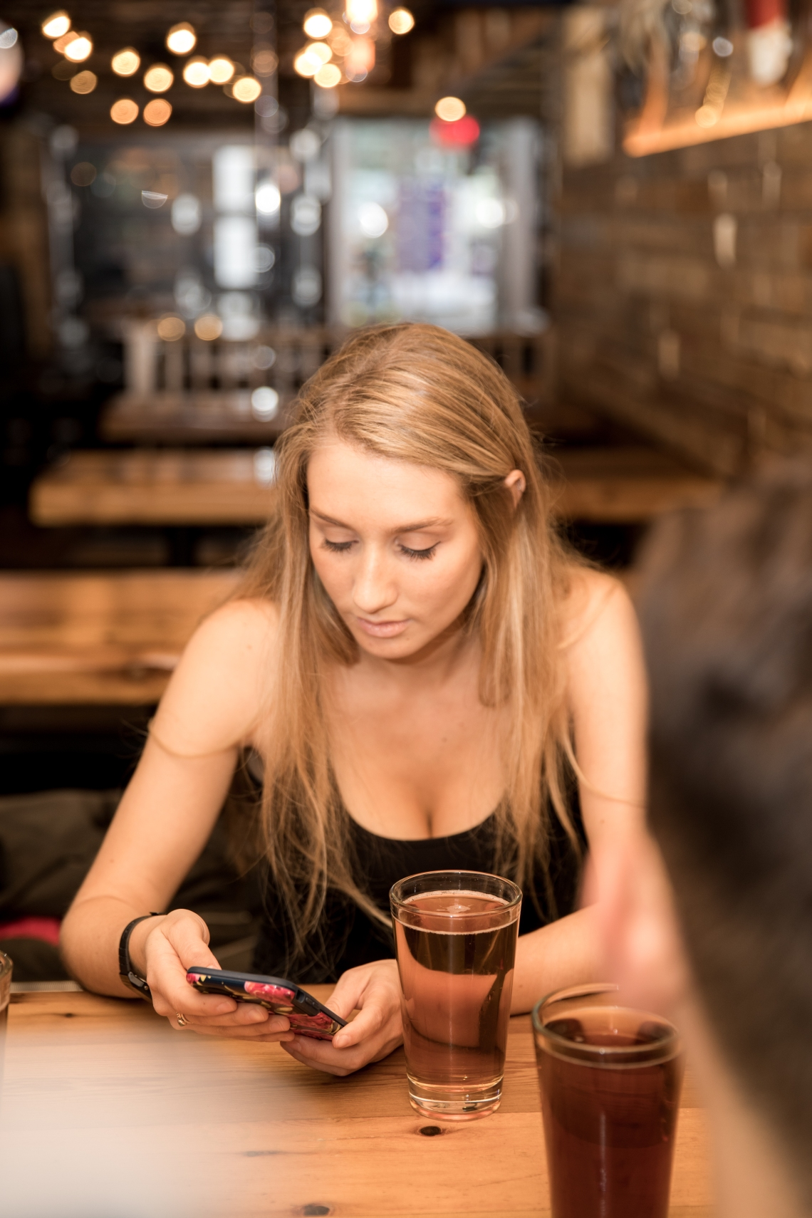 woman drinking beer and checking cell phone