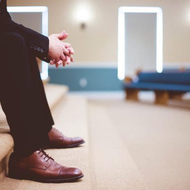 A man dressed in a suit sitting in a church