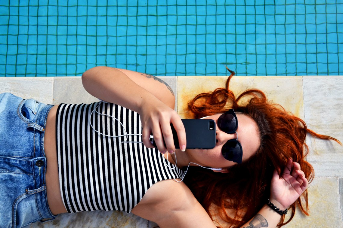 A woman lies by the pool, earphones in her hears, and texts on her iPhone