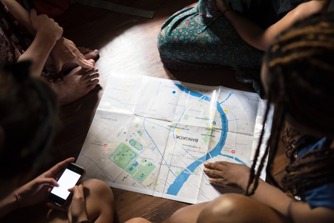 People sitting on a floor looking at a map of Bangkok