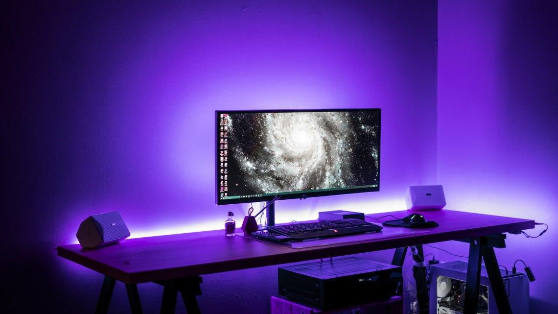 A mac desktop computer surrounded by purple light