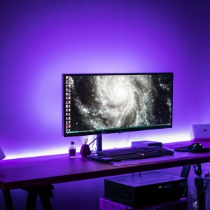 A mac desktop computer surrounded by purple light