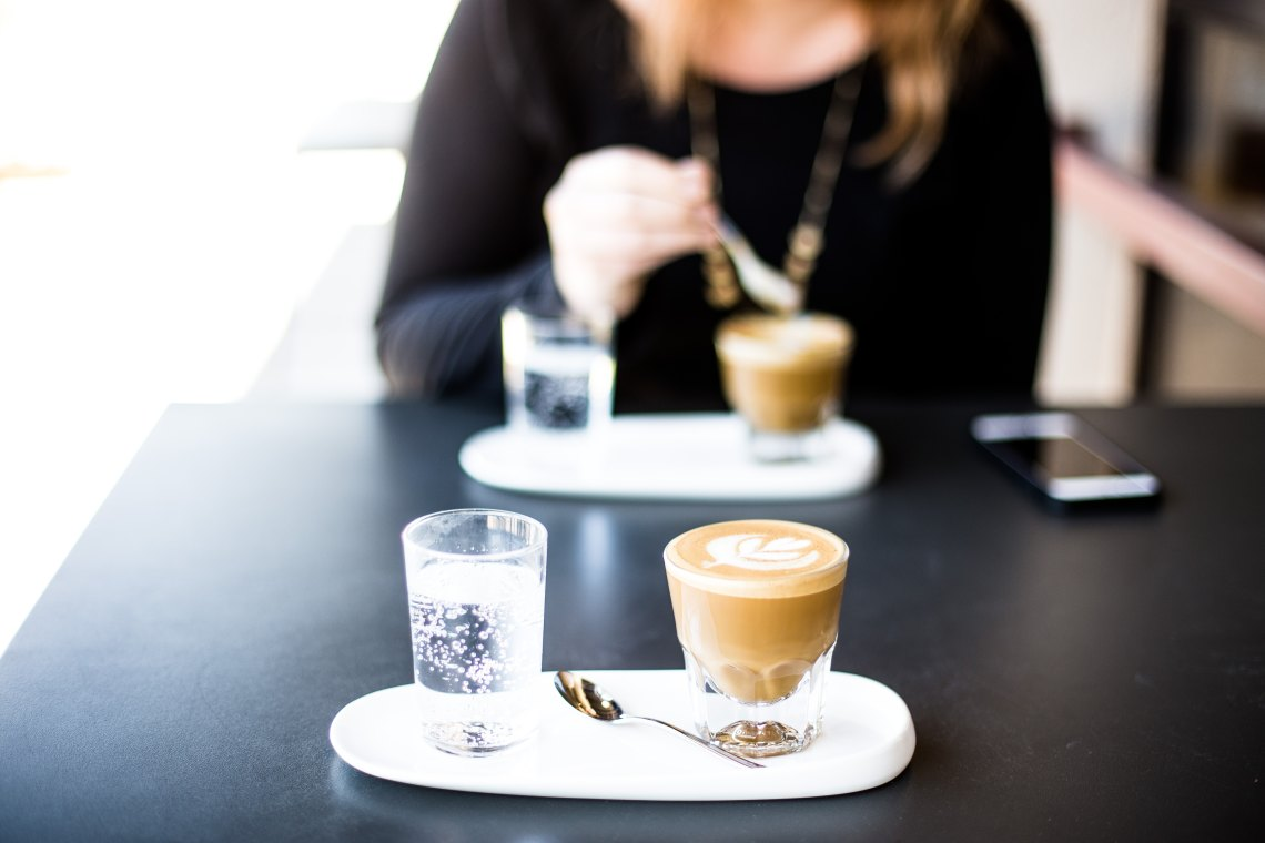 A woman sits at a table with coffee and water, looking down at her phone