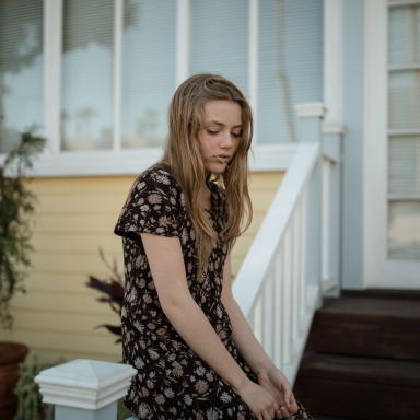 woman sitting on front railing of house looking sad