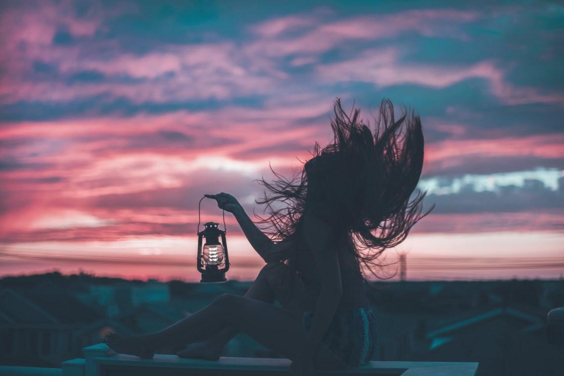 woman holding vintage lantern at sunrise