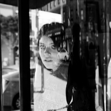woman staring out window in black and white