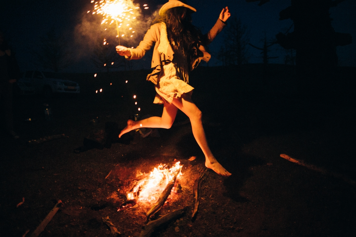woman jumping over fire
